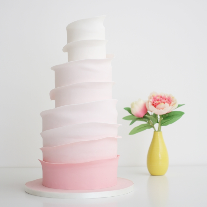 modern ombre pink layered wedding cake on white background in studio space