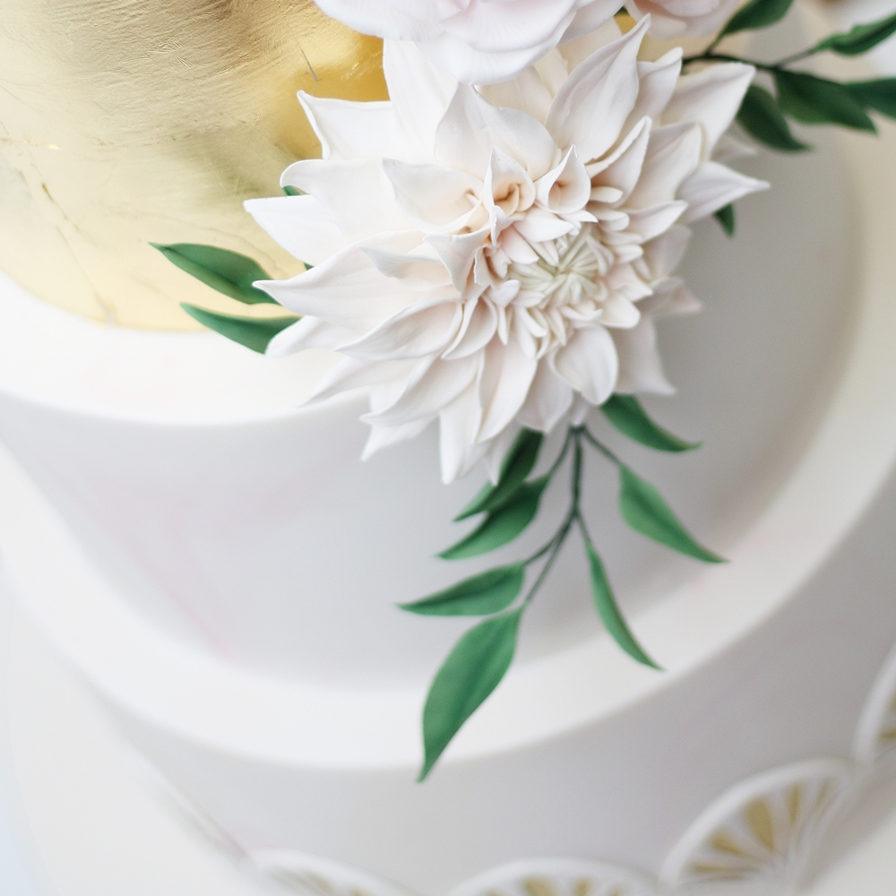 dahlia in sugar on a gold leaved cake with green leaves