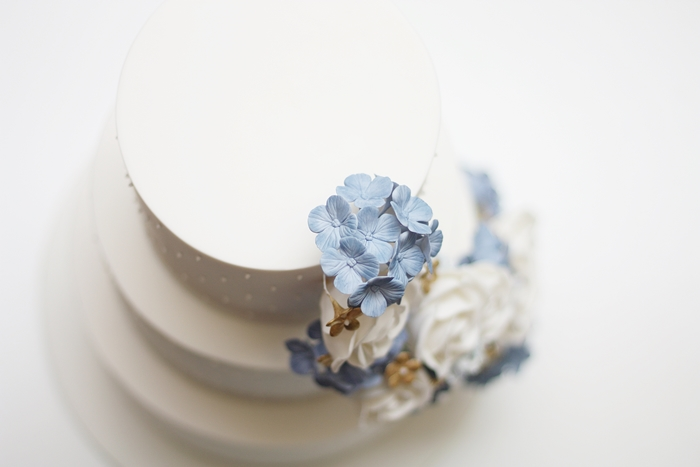 Birds eye view of white wedding cake with blue sugar hydrangeas