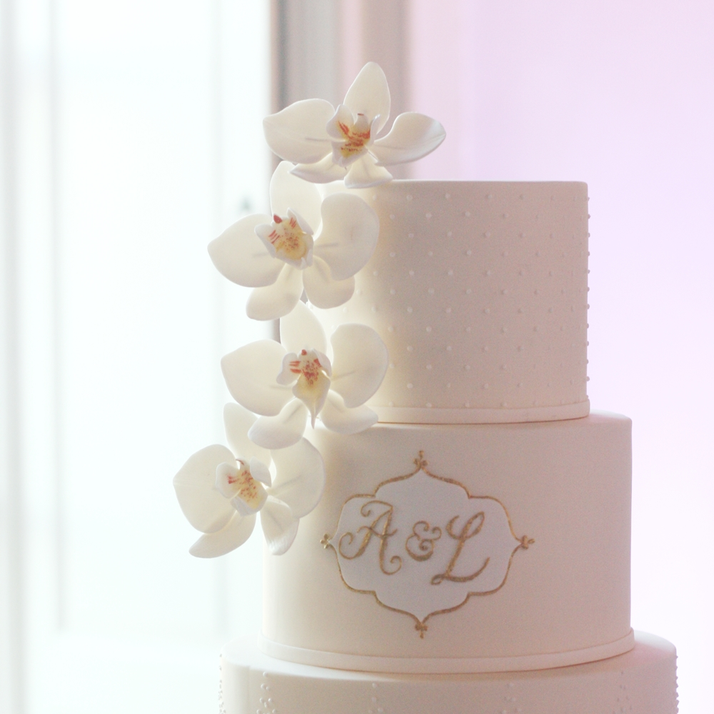 ivory cake with white orchids and monogram with gold lining
