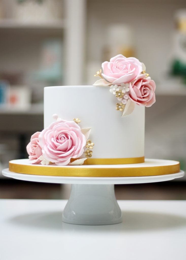 white birthday cake with pink roses